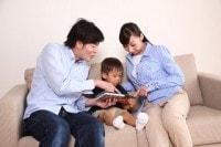 子どもと本を読む男女