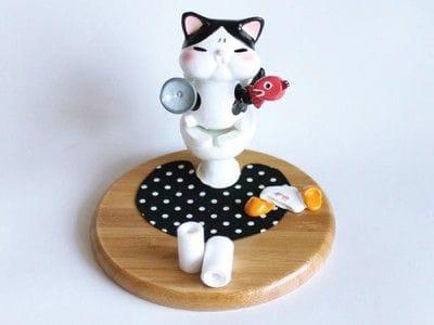 トイレに座った猫がモチーフのユニークなスマートフォン台