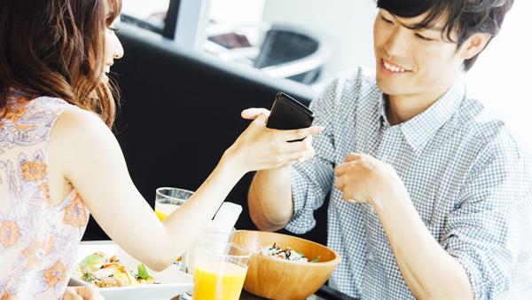 ランチデート中、携帯を見せる男女