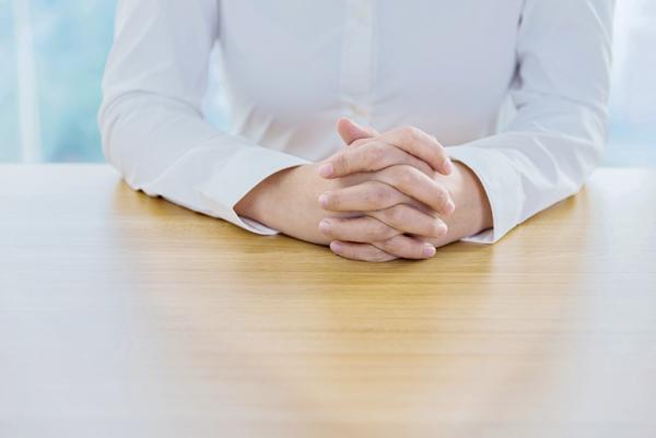 机の上で手を握っている女性
