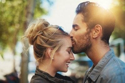 女性のおでこにキスする男性
