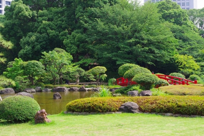 緑に映える、朱色の太鼓橋がアクセントの日本庭園。
